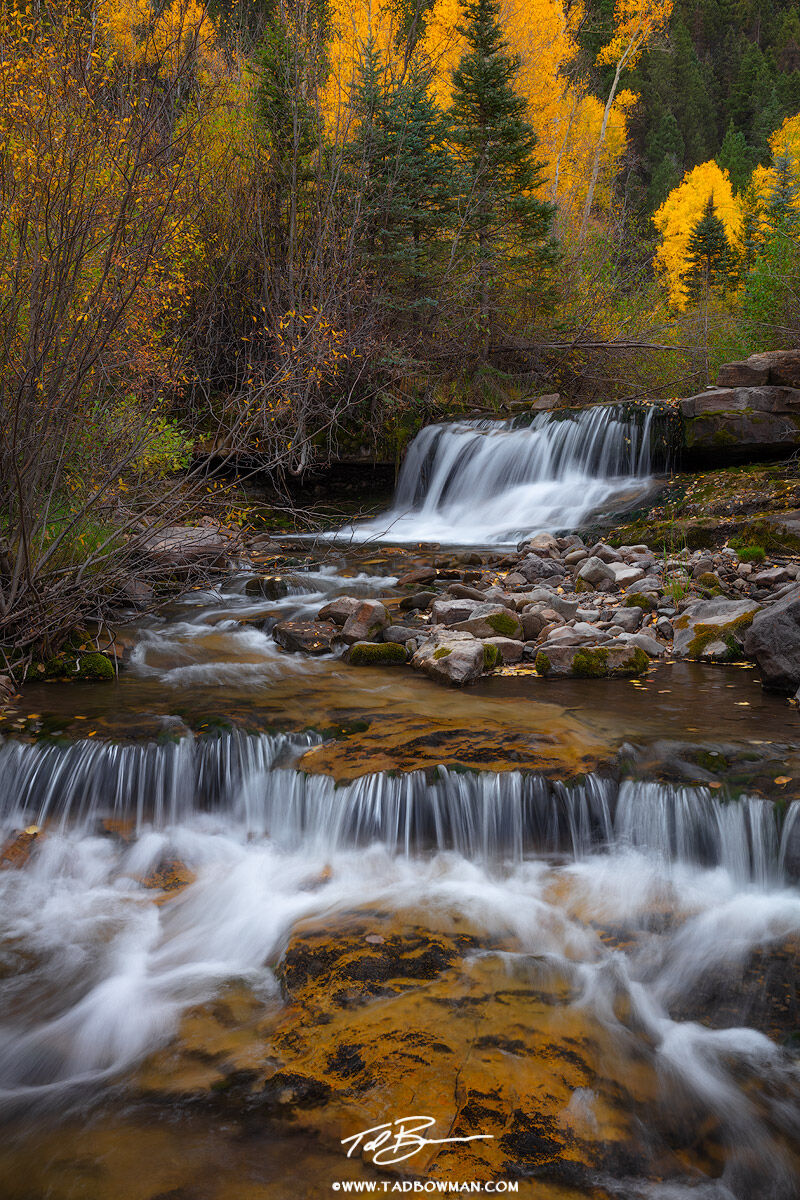 This Colorado photo depicts a waterfall with colorfall fall foliage in the background.