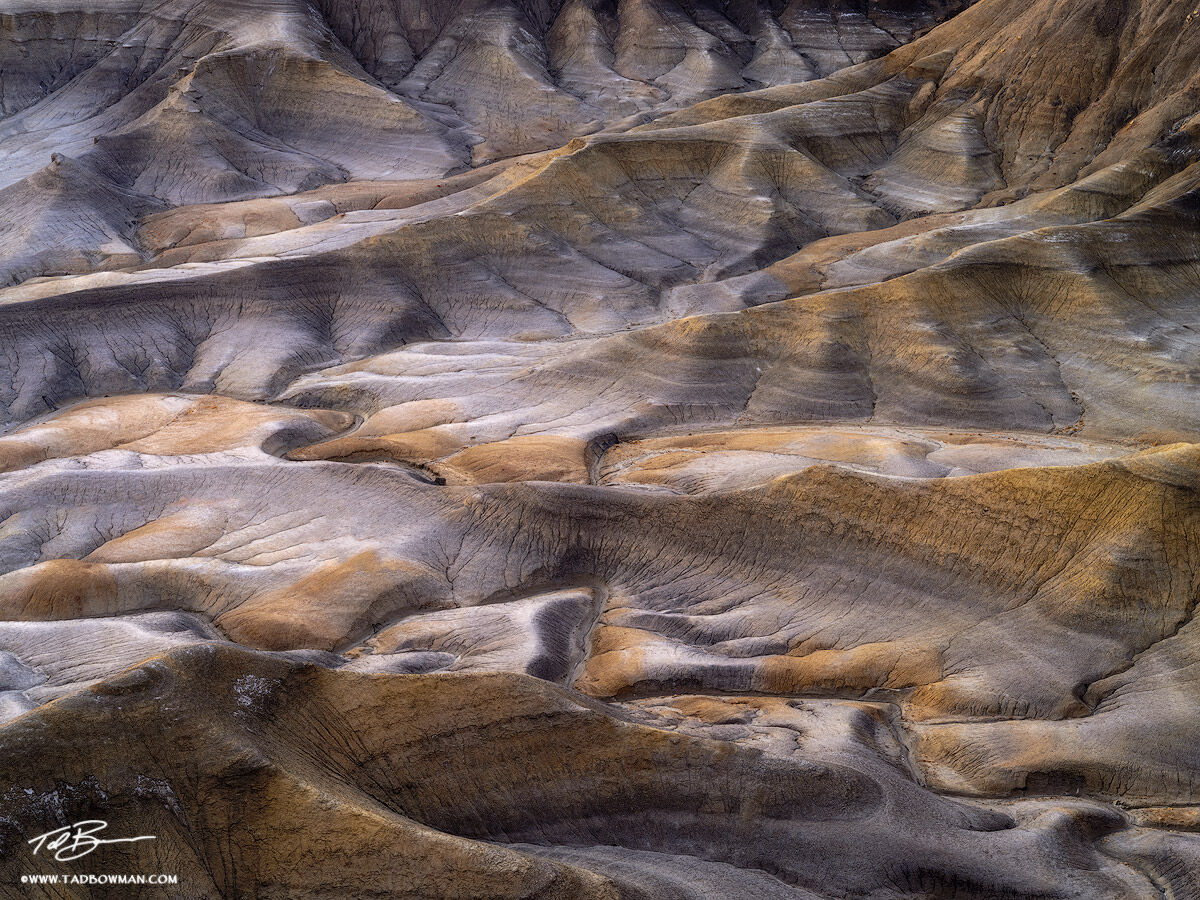 This desert photo depicts multiple pattern of lines on a canyon floor near Hanksville