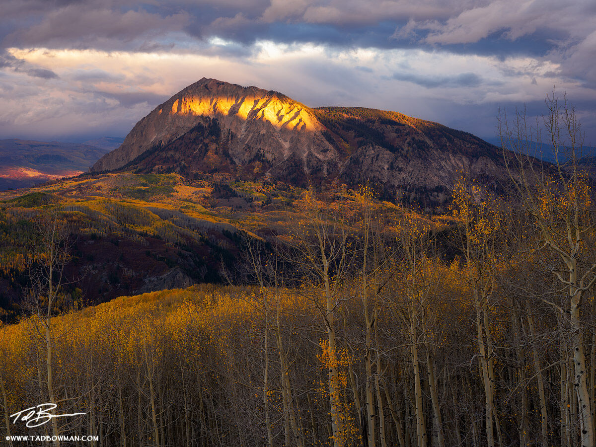 This Colorado fall photo depicts moody skies and a liver of sunshine on Marcellina Peak along with colorful fall foliage situated...