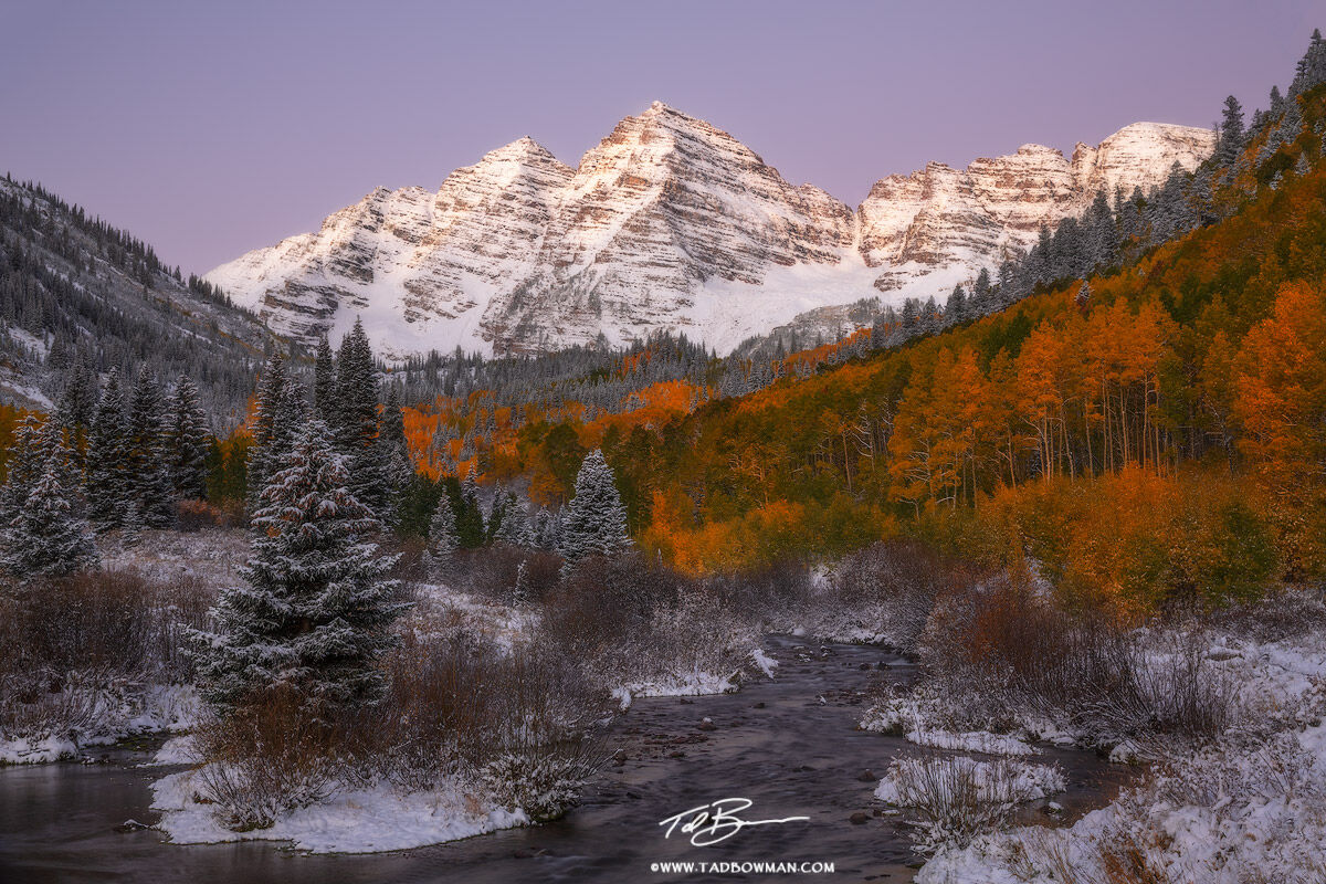 This Colorado mountain photo depicts pre-dawn light on the Maroon Bells with colorful fall foliage and a fresh snow near Aspen...