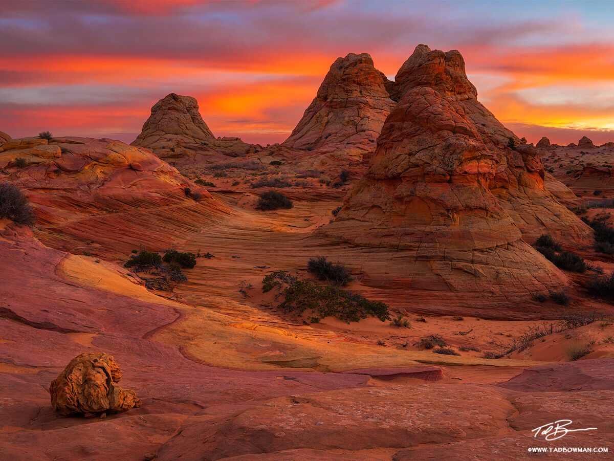 This Arizona desert photo depicts sunset overthree sandstone rock formations resembling Teepees